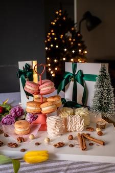 Macarons francesi, marshmallow, cannella e scatole regalo bianche sul tavolo con l'albero di natale