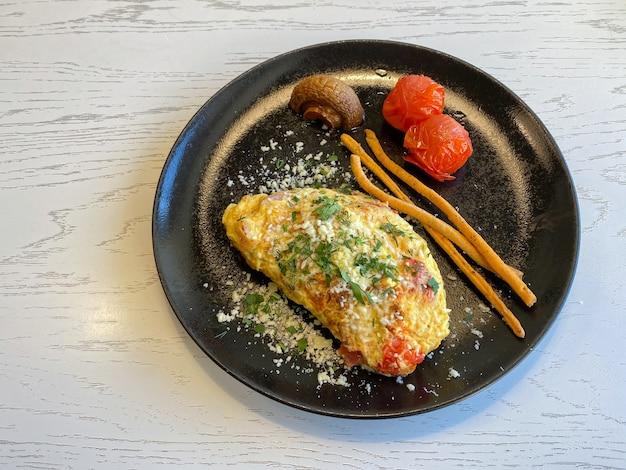Omelette francese con pancetta, pomodori, funghi e formaggio su un piatto nero