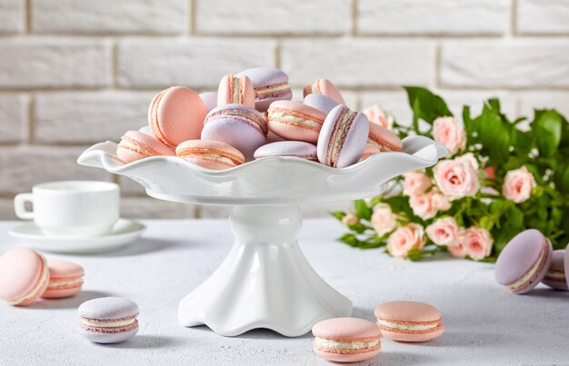 Macarons francesi rosa e lavanda su un supporto per torte