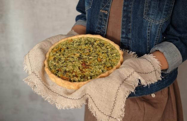 Quiche francese con pollo, funghi e broccoli nelle mani della donna