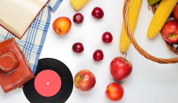 Picnic in stile retrò francese. cestino con frutta e verdura, fotocamera retrò, libro, baguette e altro sfondo bianco cibo da picnic.