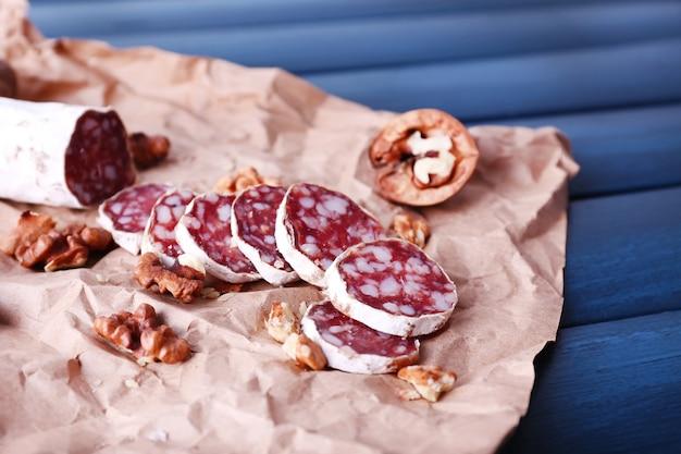 Salame francese e noci su carta artigianale su superficie di legno blu scuro
