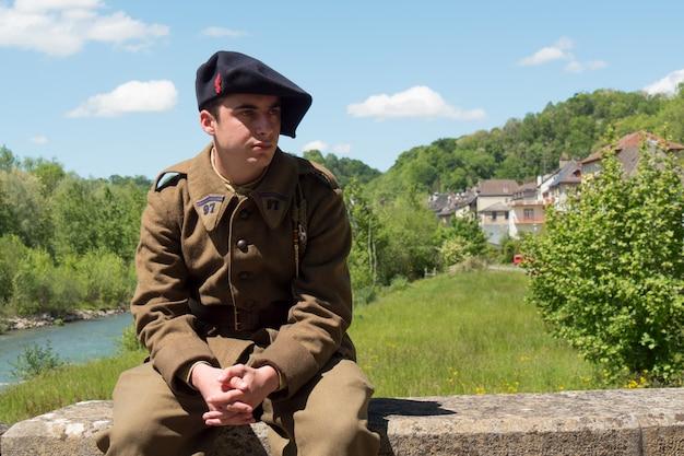 Soldato francese in uniforme degli anni '40, seduto all'aperto