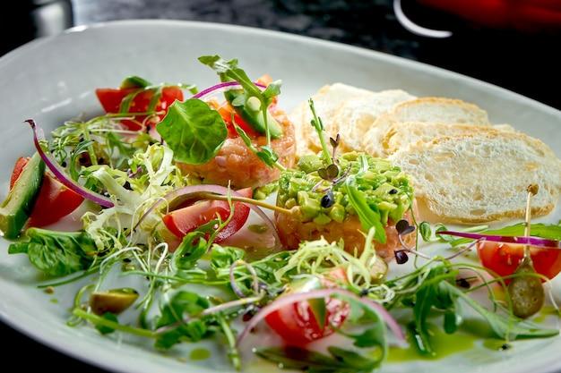 Un antipasto francese prima del piatto principale - tartare di salmone con avocado, pomodorini e crostini di pane, servito in un piatto bianco. cibo del ristorante. vista dall'alto