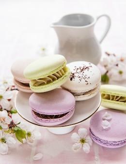 Amaretti dolci francesi varietà colorata su uno sfondo di piastrelle rosa con fiori primaverili