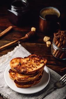 Toast alla francese su piatto bianco su superficie in legno