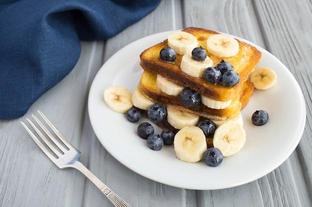 French toast con mirtilli e banana nel piatto bianco sulla superficie grigia