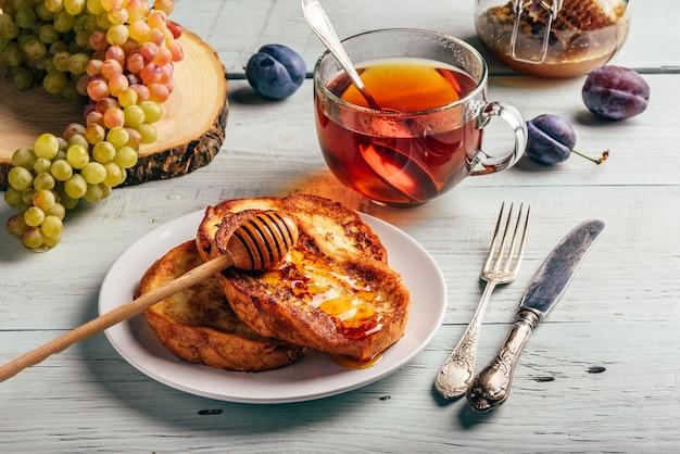 Toast francesi con frutti di miele e tè su legno bianco