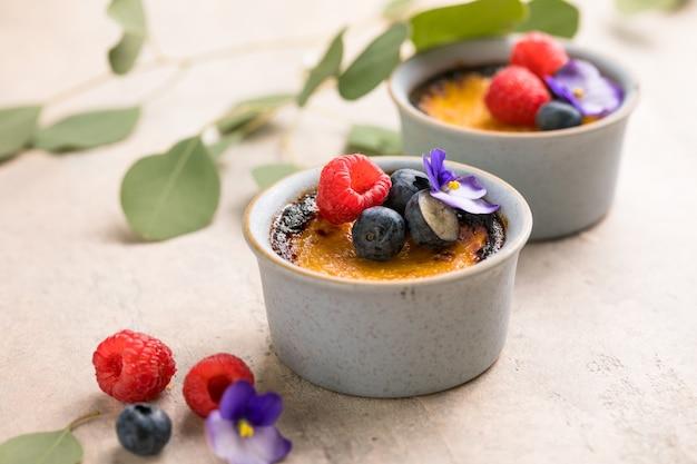 Dessert francese alla crema alla vaniglia con zucchero caramellato e frutti di bosco