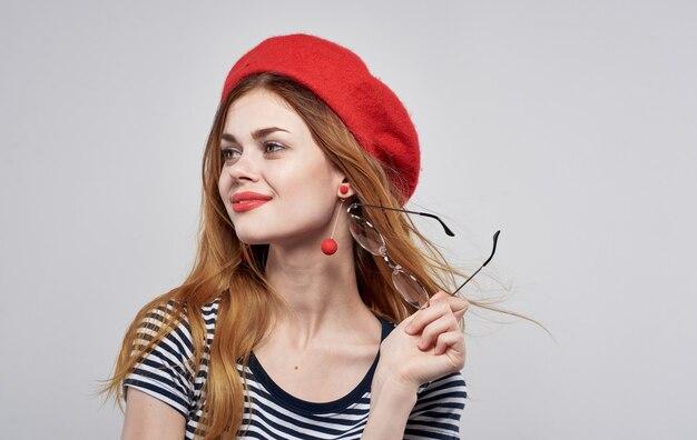 Frenchwoman in un cappello rosso e in un primo piano del ritratto di modello di occhiali t-shirt a strisce.