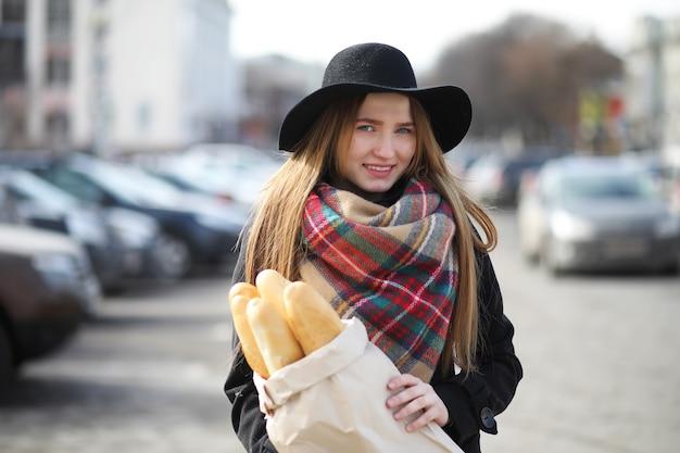 Francese con baguette nella borsa mentre esce dal negozio