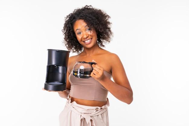 La donna africana fresca in estate copre con la macchinetta del caffè, immagine isolata sulla parete bianca