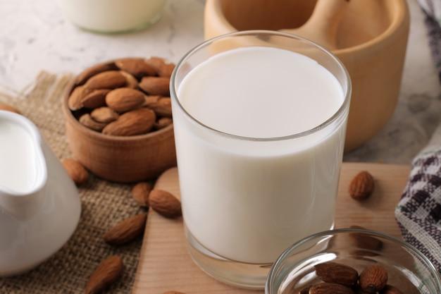Latte di mandorle fresco in un bicchiere e noci di mandorle su sfondo chiaro