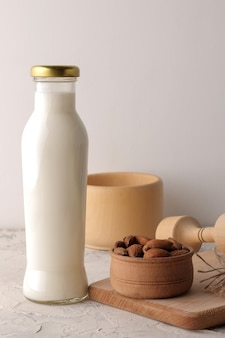 Latte di mandorle fresco in una bottiglia di vetro e noci di mandorle su uno sfondo chiaro