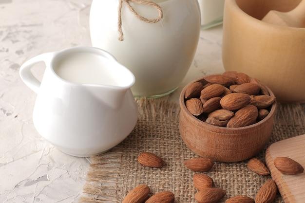 Latte di mandorle fresco in una brocca di latte e noci di mandorle su uno sfondo chiaro