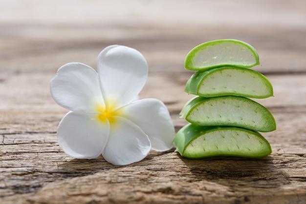 La stazione termale fresca di alo vera e di plumeria fiorisce sulla tavola di legno, sul trattamento della stazione termale e sul concetto di cura di pelle del corpo