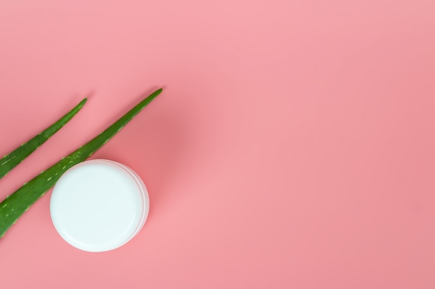 Foglie fresche di aloe vera e vaso cosmetico di plastica bianco su sfondo rosa pastello per prodotti di bellezza e salute.