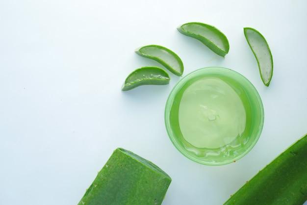 Aloe vera fresca a fette e gel liquido in un contenitore di plastica su sfondo bianco