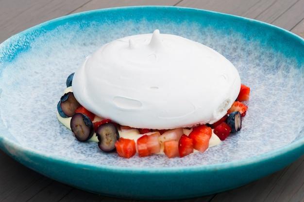 Dessert fresco di anna pavlova con frutti di bosco in un piatto blu