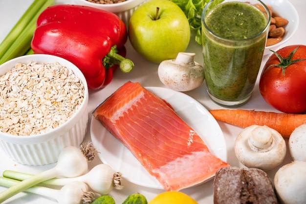 Salmone fresco appetitoso e altri ingredienti per cucinare su un cibo da tavola bianco e una dieta sana