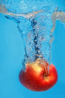 Mela fresca scende in acqua con spruzzata su uno spazio blu