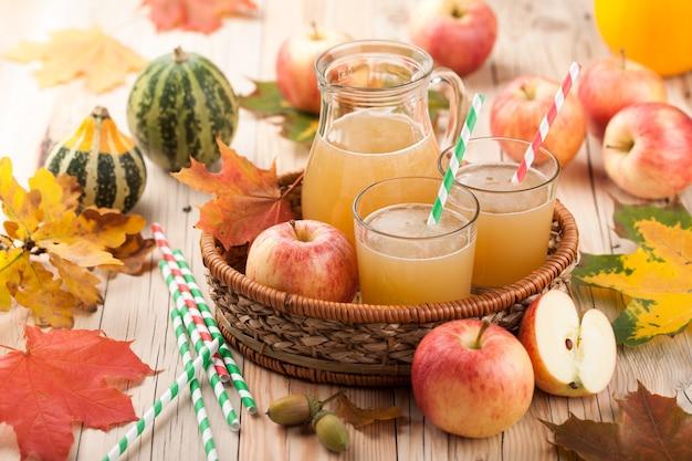 Succo di mela fresco, mele, zucche e foglie autunnali colorate su un tavolo di legno