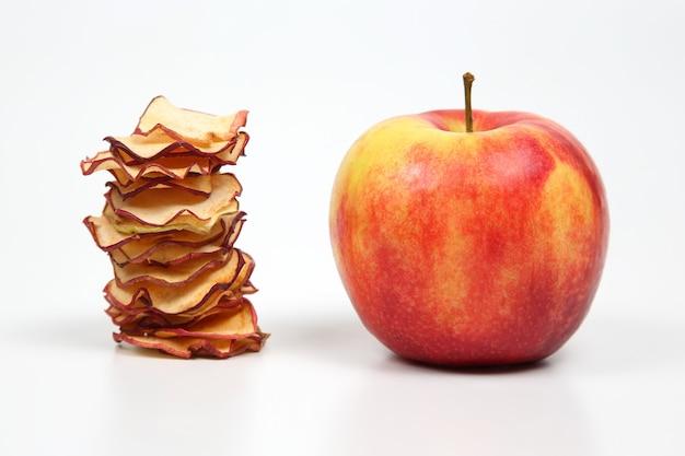 Mela fresca e una pila di fette di mela secche su bianco