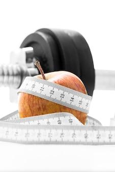 Mela fresca avvolta in un metro a nastro con un peso in palestra. perdita di peso, salute, dieta e concetto di fitness.