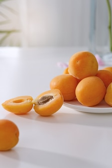 Albicocche fresche in un piatto su un tavolo bianco. sfondo chiaro.