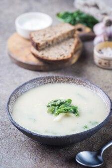 Zuppa di crema di asparagi freschi in una ciotola sul tavolo di pietra grigia