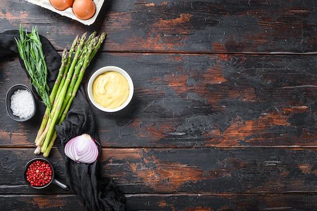 Uova fresche di asparagi e ingredienti per condire francese con senape di digione, dragoncello di cipolla su vecchio fondo di legno scuro, vista dall'alto con spazio per il testo.