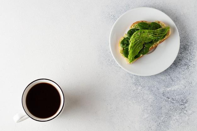 Avocado fresco su fondo concreto luminoso con la vista superiore della tazza di caffè nero.