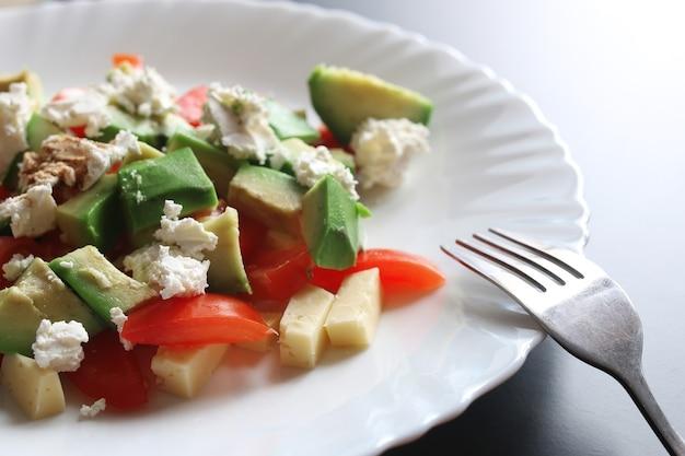 Avocado fresco deliziosa insalata mediterranea con pomodorini e mandorle e parmigiano feta