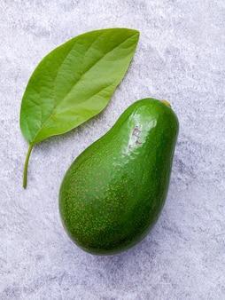Avocado fresco impostato su sfondo di pietra bianca. l'avocado è popolare per la cucina alimentare sana e il controllo del peso.