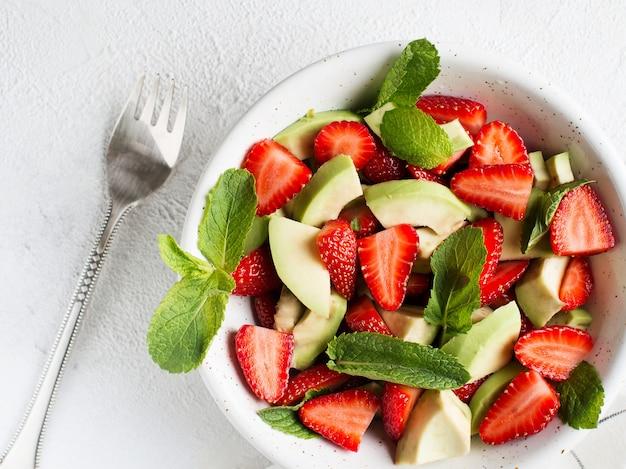 Insalata fresca di avocado e fragole con foglie di menta su sfondo bianco
