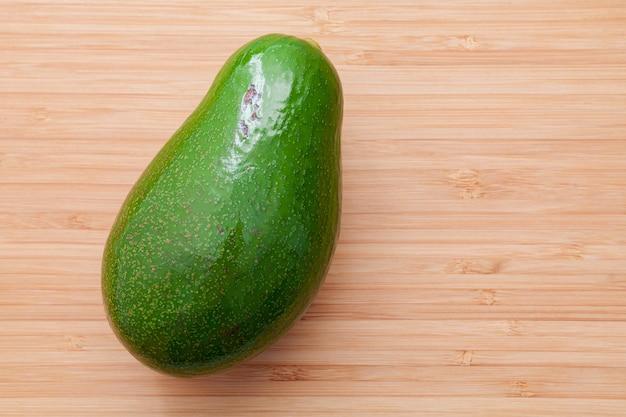 Avocado fresco su fondo di legno. concetto di cibo sano di avocado biologico. avocado su tagliere di bambù. l'avocado è popolare nella cucina vegetariana e nel controllo del peso.