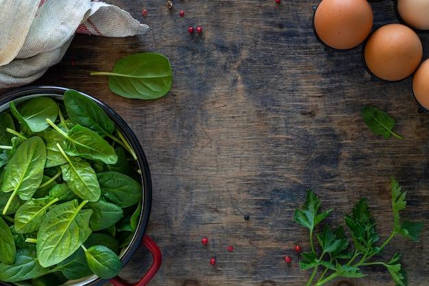 Foglie di spinaci freschi in una ciotola e uova su un tavolo di legno. vista dall'alto. copia spazio