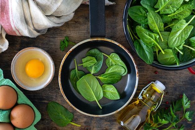 Foglie di spinaci freschi in una ciotola e uova su un tavolo di legno. vista dall'alto.