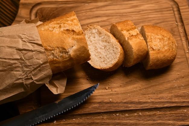 Baguette fresche in un pacchetto artigianale parzialmente affettato e coltello da pane sul tagliere di legno