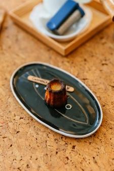 Canelés appena sfornato, una piccola pasticceria francese aromatizzata al rum e alla vaniglia con un morbido e tenero centro di crema e un buio