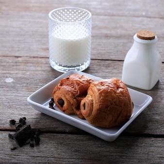 Croissant al cioccolato appena sfornato (pain au chocolat) con latte per colazione. servito su piastra bianca su tavola rustica copia spazio per il testo