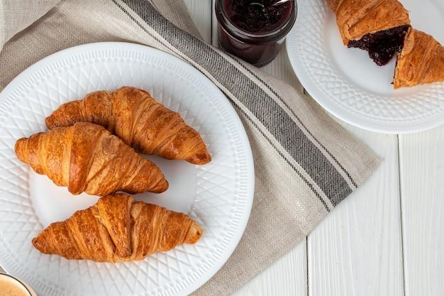 Croissant appena sfornato sulla tavola di legno si chiuda