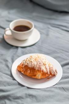 Croissant francesi al forno freschi e una tazza di forte caffè aromatico sul letto grigio di mattina.