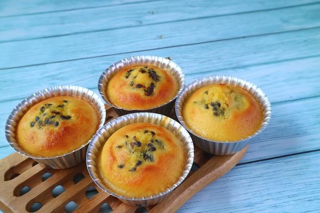 Muffin fatti in casa freschi del frutto della passione in stampi sulla tagliere di legno