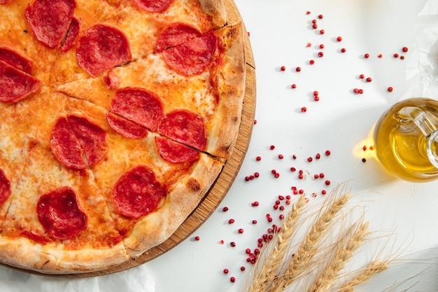 Pizza ai peperoni al forno fresca su priorità bassa bianca