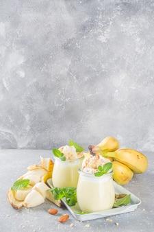 Budino di banana fresca per colazione, yogurt alla banana. dessert dolce in bicchieri con fette di banana e noci, spuntino vegetariano crudo