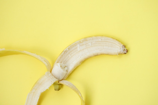 Banana fresca su sfondo giallo. modello senza cuciture con le banane. sfondo astratto tropicale. banana su sfondo giallo. banana sbucciata su sfondo giallo
