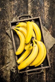 Banane fresche su un vecchio vassoio. su uno sfondo di legno.