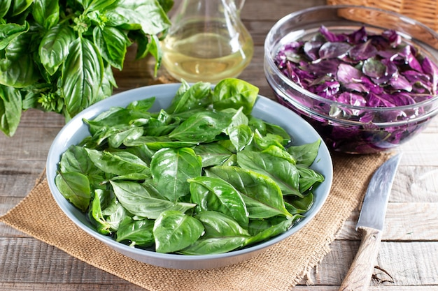 Foglie di basilico fresco in una ciotola con acqua su un tavolo di legno. basilico verde e viola. concetto di una sana alimentazione.