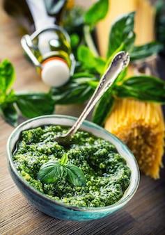 Il basilico fresco lascia l'aglio e gli spaghetti al pesto sulla tavola di legno.